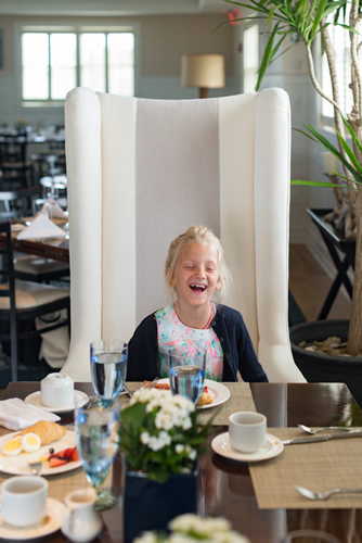 Girl Sitting in Big White Chair & Laughing During Dinner at The Dunes Restaurant at the Winnetu
