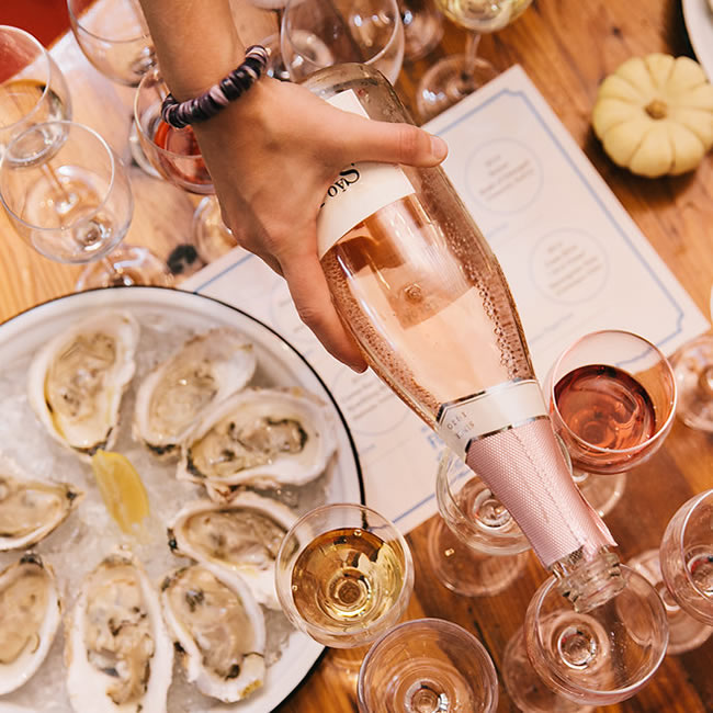 Bottles of Wine Being Poured Into Glasses Together With Oysters on the Half-Shell on White Plates